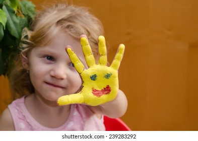 blond girl with painted sun on her hand