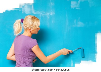 Blond girl painting wall with blue paint.