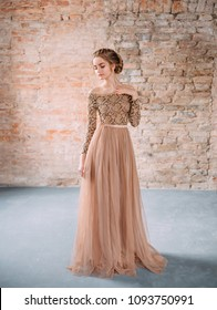 A blond girl is posing in a soft sandy, brown dress with a lace top and with a sumptuous tulle skirt. The image of the party, or graduation. The hair is gathered in an elegant bun, with soft curls
