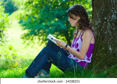 Blond girl reading a book in a park