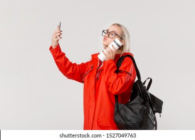 Blond girl in a red raincoat and glasses making selfie with a smartphone travelling with black backpack and white thermal mug in cold season. Rainy season.