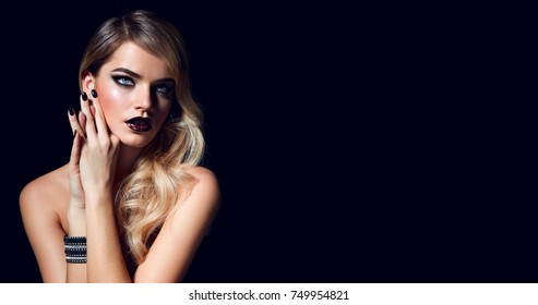 Blond girl in a rock style with makeup smoky ice in the studio on a black background.