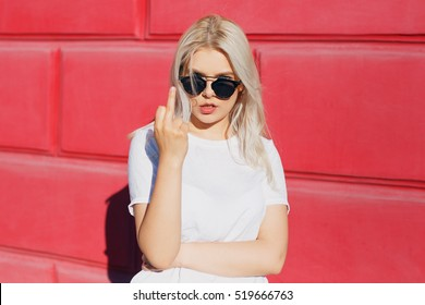 Blond girl showing middle finger you gesture over red color background. Rude teenager swag style
