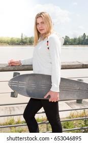 blond girl with skate longboard in city near river