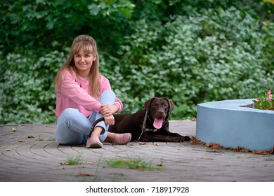 blond girl smiling with a dog Labrador. Labrador lying next to a young woman.