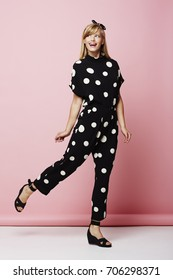 Blond girl in spotted jumpsuit posing in pink studio