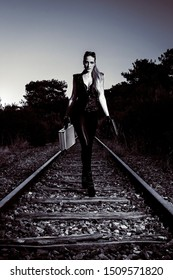 Blond girl with suitcase walking on the abandoned railway. Sexy woman in black leather clothes with gun at night. Criminal gangsta woman escape from mafia. Secret agent with weapon.