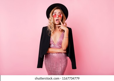 Blond girl with surprise face  standing over pink background . Wearing elegant dress with sequins . Amazed emotions.