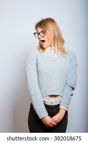 blond girl is tired and yawning, wearing glasses isolated on a gray background