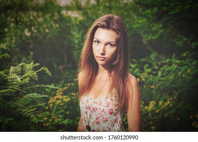 Blond girl wearied in boho dress and jevelry posing in the bushes in summertime. She is looking at camera seriously.