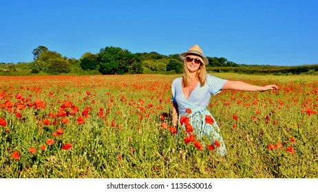 Blond Girl wearing a  hat in summer in field of red flowers. Dalkeith, Scotland UK. jULY 2018