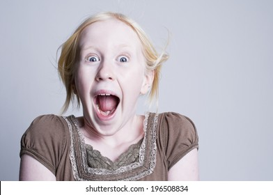 A blond girl wearing a shirt looking surprised.