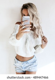 Blond girl wearing white sweater and jeans shorts making selfie by her smartphone in the mirror. Blogger taking photo of self fashion look.