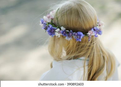 Blond girl with a wreath of living wild flowers on his head. Russian style.