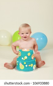 Blond hair blue eyed baby boy being cheeky smiling and pulling silly faces by his blue yellow green and orange two tier birthday party cake while sitting on a cream background with balloons behind