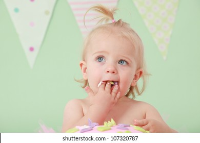 Blond hair blue eyed baby girl with pony tail eating and tasting vanilla sponge cake with pink and purple fondant icing while sitting on green background with pink green white and blue flag bunting