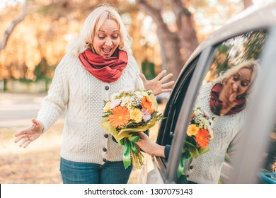 Blond hair excited middle-aged lady looking surprised at the flower bouquet given by her man who sits in a car - spring, date and women's day celebration concept
