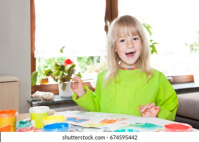 Blond hair girl with painting with watercolors on the table in the room.