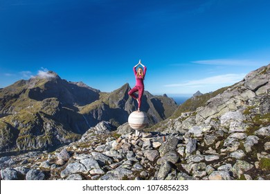 The blond hair girl is standing in yoga position asana vrikshasana on stone sphere - Jupiter monument in mountains on Munkan mountain on the Lofoten Islands beyond the Arctic circle in Nordic Norway