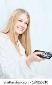 Blond hair woman in bathrobe holding remote controller