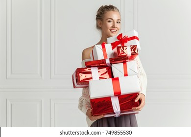 Blond hair woman in white sweater holding a lot of presents over white wall background indoor. Smiling woman holding paper gift boxes red color and looks at camera. Toothy smiling woman's face.