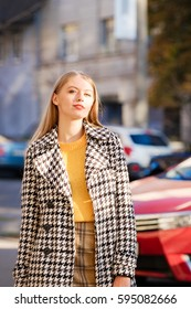 Blond hair young woman model posing in the city. Street fashion style concept.