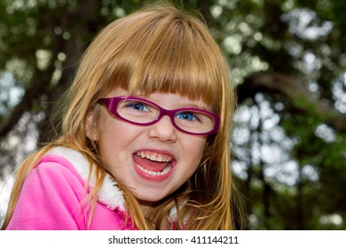 A blond haired, blue eyed, little girl with a hug, open mouth smile and big, bright eyes.  She looks extremely happy and possibly a bit surprised.