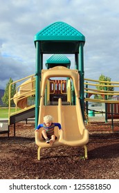 Blond haired child at the playground with dramatic cloudy sky, Utah, USA.