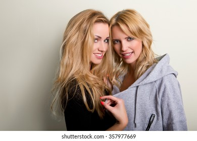 blond haired girls friends laughing and hug