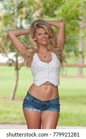 A blond haired model posing in or around a barn