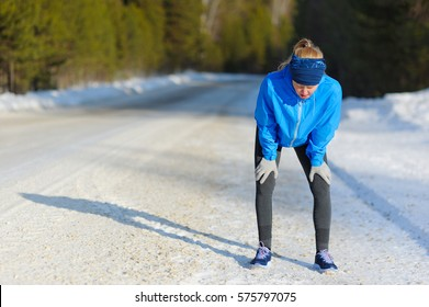 Blond haired woman having a rest after hard workout on a winter road. Healthy and sporty Lifestyle.