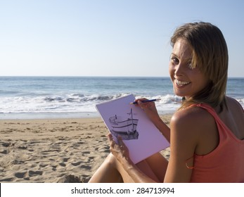 blond happy girl drawing a boat in the beach at summer during her holidays