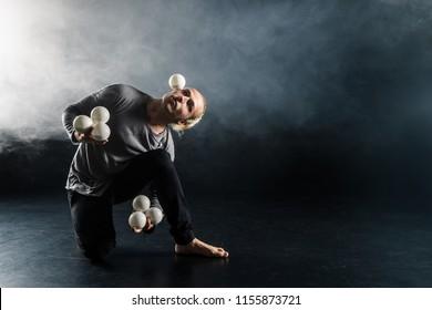 Blond juggler with white balls on black background