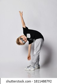 Blond kid boy in sunglasses, black t-shirt, gray pants and sneakers does gymnastics bending exercises tilts body forward arms spread wide over gray background
