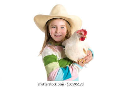 Blond kid girl farmer holding white hen on arms with cowboy hat