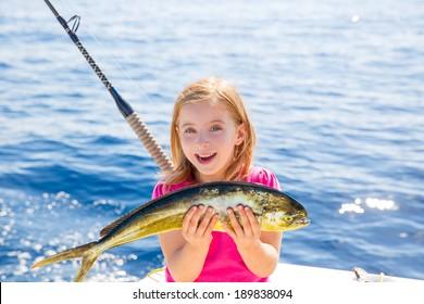 Blond kid girl fishing Dorado Mahi-mahi fish happy with trolling catch on boat deck