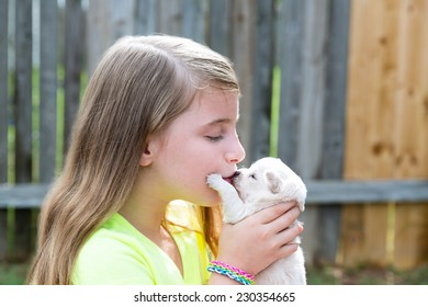 Blond kid girl kissing puppy pet chihuahua playing happy with doggy outdoor
