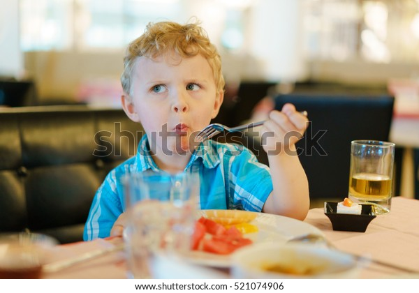 Blond kid tries breakfast fruits with suspicious wary expression on his face. He keeps fork in his hand. Dressed in a blue shirt. Fruit bowl, small cake and glass of juice on a table.