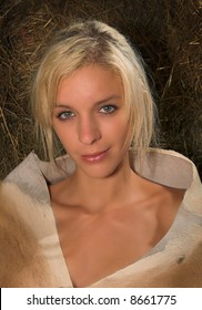 a blond lady is sitting in a barn on bales with just an animal skin of a Springbok around her shoulders.