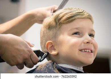 Blonder kleiner Junge, der im Friseur einen Haarschnitt bekommt.
