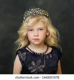 Blond Little Girl  in crown over dark background fashion kid
