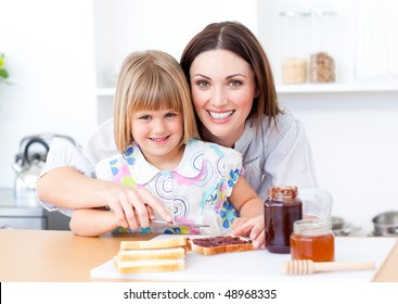 Blond little girl and her mother preparing toasts in the kitchen