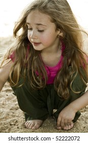 Blond little girl with long hair playing in the sand