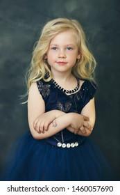 Blond Little Girl over dark background
