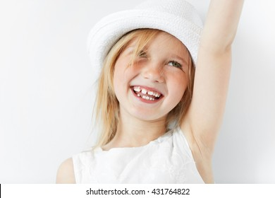 Blond little girl in white morning light stretching her arm up in cheerful mood like celebrating her victory. Smiling child looking up showing her infant teeth and positive emotions.