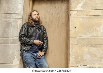 Blond long hair and beard young adult hipster man listening music. Outdoor, urban scene.