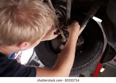 A blond male mechanic inspecting a CV joing on a car