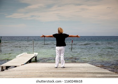 Blond man with black shirt, white pants and stretched arms enjoys the moment on a wooden pier on the Mediterranean coast