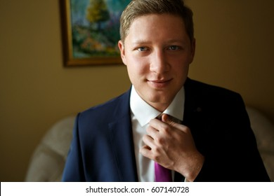 Blond man with blue eyes fixes violet tie