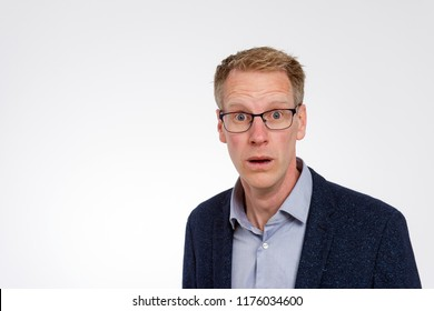 Blond man with glasses is thunderstruck because of an unpleasant announcement.